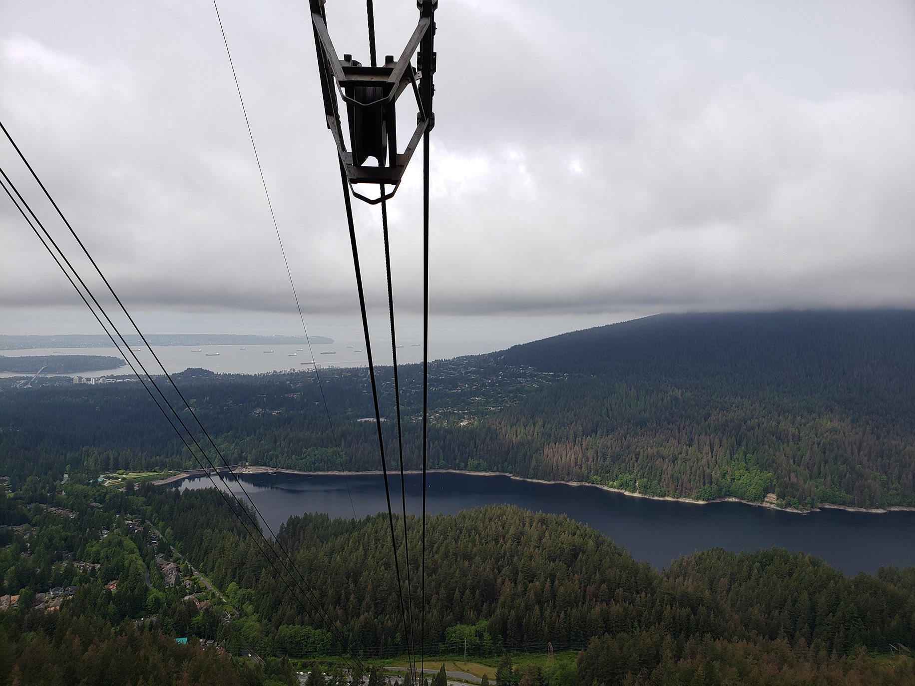 A view from the Grouse Mountain gondola showing the Capilano Lake dam, Stanley Park, and the Lions Gate Bridge.